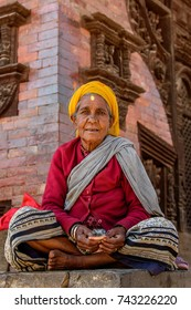 KATMANDU, NEPAL - MAR 6, 2017: Unidentified Chhetri old woman in traditional clothes and headscarf sits on the ground in lotus position. Chhetris is the most populous ethnic group of Nepal