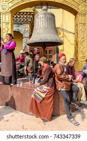 KATMANDU, NEPAL - MAR 6, 2017: Unidentified Chhetri people sit on the pedestal under the big bell. Chhetris is the most populous ethnic group of Nepal