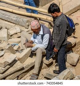 KATMANDU, NEPAL - MAR 6, 2017: Unidentified Chhetri man holds a hammer and nails. Chhetris is the most populous ethnic group of Nepal