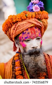 KATMANDU, NEPAL - MAR 6, 2017: Unidentified Chhetri old man with beard and painted face wears orange costume, a hat and different necklaces. Chhetris is the most populous ethnic group of Nepal