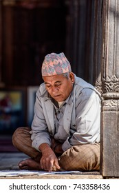 KATMANDU, NEPAL - MAR 6, 2017: Unidentified Chhetri man sits on the ground and reads a paper. Chhetris is the most populous ethnic group of Nepal