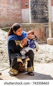 KATMANDU, NEPAL - MAR 6, 2017: Unidentified Chhetri woman in traditional clothes holds a baby. Chhetris is the most populous ethnic group of Nepal