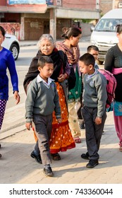KATMANDU, NEPAL - MAR 6, 2017: Unidentified Chhetri two boys in grey sweaters stand before old woman on the street. Chhetris is the most populous ethnic group of Nepal