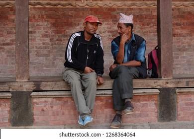 Katmandu, Nepal - Oct 9 2014: Men taking break to gossip and chit chat at the Royal Durbar Square of Nepal, Katmandu.