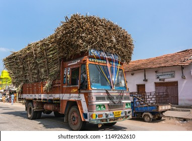 Katnalhantha, Karnataka, India - November 1, 2013: Orange large Ashok-Leyland truck heavily overloaded with brown sugar cane stalks rides through the town under blue sky.