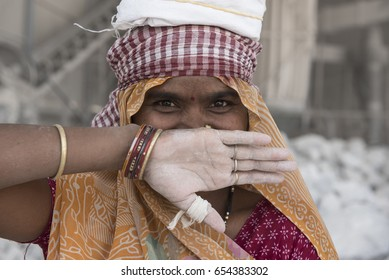 Katni / India 10  May 2017   portrait of a woman laughing and covered her mouth with hands in stone crushing factory  at  Katni  Madhya Pradesh India