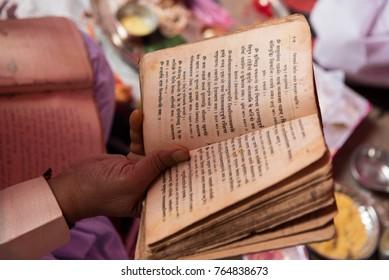 katni / India 22 November 2017 Priest reading various rituals from book in Indian Hindu wedding at Katni  Madhya Pradesh India