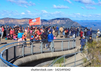 Katoomba / Australia - May 26 2019: Sightseers on Echo Point in the Blue Mountains, Australia. A Group of Chinese Tourists are Waving a Flag With Chinese Characters