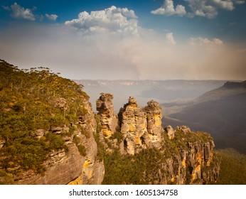 Katoomba, New South Wales / Australia - January 4th 2020: Green Wattle Creek bush fire in the Blue Mountains forms pyrocumulonimbus cloud behind three sisters landmark.