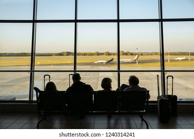 KATOWICE AIRPORT, POLAND - OCTOBER 15, 2018: Tourists sitting in the airport with suitcases. People are waiting for the flight. Travel concept photo. Delayed plane.