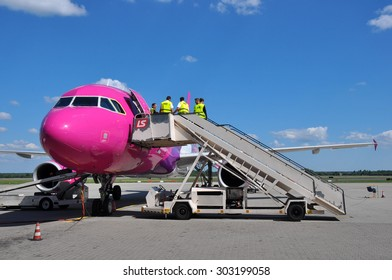 KATOWICE - JULY 2: Cabin crew staff entering the Wizzair Airbus A320 before the flight on July 2, 2015 in Katowice Airport, Poland. Wizzair is one of the largest low-cost airlines.