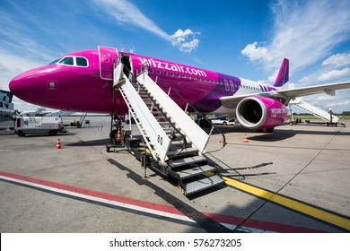 Katowice, Poland - AUGUST 18, 2014: Airbus A320 Wizz Air with attached passenger boarding stairs. Airport equipment.