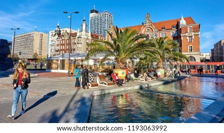 KATOWICE, POLAND - SEPTEMBER 30, 2018: Main square on 30 September 2018 in Katowice, Poland. At the large fountain in the city center under the palm trees rest the inhabitants