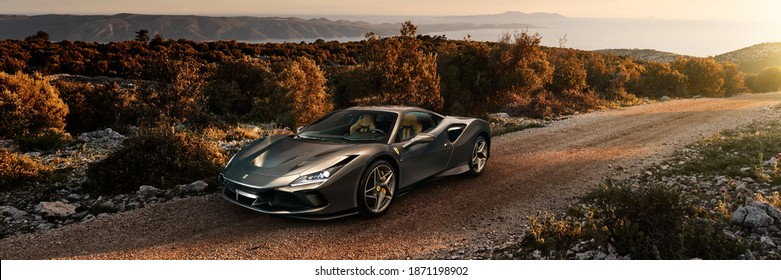 Katowice, Poland-06.14.2019: Ferrari F8 Tributo on a gravel road on the island of Brac in Croatia. In the background there is a view of the Adriatic Sea. Electronic assembly car and landscape.