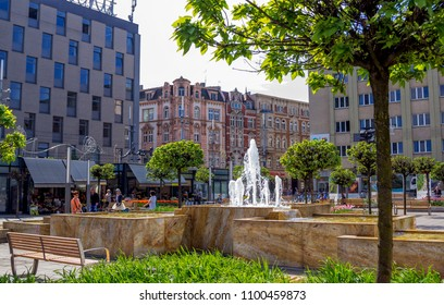Katowice/Poland- April 30, 2018: view of Katowice city center with old historical and modern buildings, fountain, green trees, flowers and walking people.