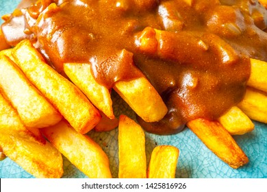 Katsu curry sauce with onions on french fries / chips.
