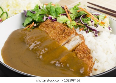Katsu Kare - Japanese breaded deep fried  pork cutlet  (tonkatsu) served with shredded cabbage, steamed rice, salad and curry sauce.