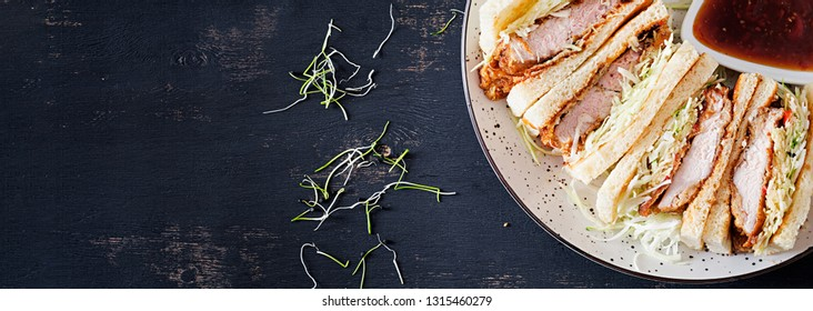 Katsu Sando - food trend japanese sandwich with breaded pork chop, cabbage and tonkatsu sauce. Japanese cuisine. Top view. Banner