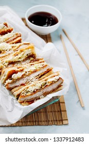 Katsu Sando - traditional japanese cutlet sandwich with deep fried pork,cabbage,japanese mayonnaise and tonkatsu sauce on a light background close-up.Food trend - Asian food.Japanese fast food