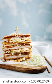 Katsu Sando - traditional japanese cutlet sandwich with deep fried pork,cabbage,japanese mayonnaise and tonkatsu sauce on a light background close-up with copy space for text.Japanese fast food