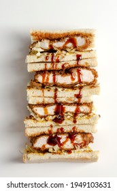 Katsu sandos japanese sandwich with chicken or pork chop, cabbage and tonkatsu sauce isolated on white.