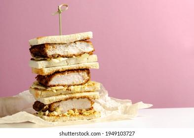 Katsu sandos japanese sandwich with chicken or pork chop, cabbage and tonkatsu sauce isolated on pink background.