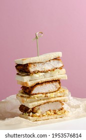 Katsu sandos japanese sandwich with chicken or pork chop, cabbage and tonkatsu sauce isolated on pink background.