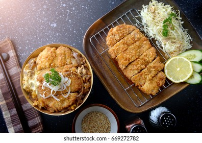 Katsudon or Japanese style fried pork roast with eeg and Japanese ingredient mixed on rice ready to serve in studio low lighting.