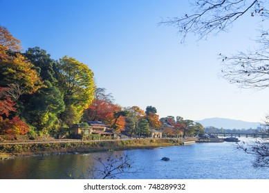 The Katsura river in Arashiyama area in autumn, Kyoto, Japan, with the Togetsukyo Bridge in the distance.