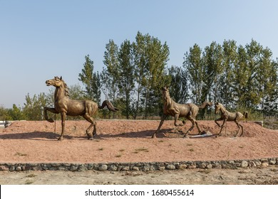 Katta Turk, Uzbekistan - October 18, 2019: A statue of running horses on the side of the road in the Dangara district of the Ferghana region.