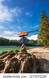 Katun tourist base, Katun River, Chemal district, Altai Mountains, South Siberia, Russia-August 25, 2018: guitar monument on the river Bank