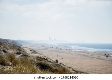 Katwijk aan Zee, South-Holland, The Netherlands, 02-28-21: Lot's of people walking on the beach during covid-19 with the skyline of Scheveningen in foggy weather in the background