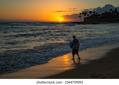 Kauai, Hawaii - 2/23/2016:  A young man with boogie board at sunset on the wet sand on Poipu beach, Kauai, Hawaii