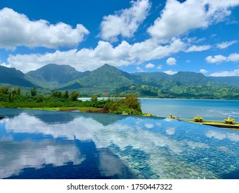 In Kauai, a photo of clouds off of a reflecting pool with a view of the mountains in the background.