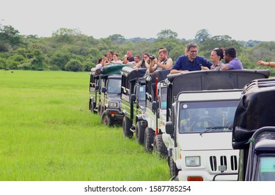 KAUDULLA NATIONAL PARK, SRI LANKA - November 1,2019. Tourists in crowded row of safari jeeps are taking pictures of wildlife animals in nature landscape at 4x4 offroad track. Explore the world concept