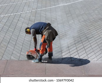 KAUNAS, LITHUANIA - CIRCA APRIL 2017: unidentified road worker with a cutting wheel