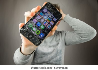 KAUNAS, LITHUANIA - DECEMBER 5, 2016: Desperate and astonished man holds cracked smartphone . Screen broken smartphone. Cracked iphone 4. Broken phone