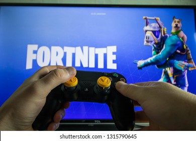 KAUNAS, LITHUANIA - FEBRUARY 17, 2018: Most popular battle royale game Fornite. Ps4 controller and video game in the background