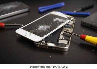 Kaunas, Lithuania - February 24, 2021: Broken Iphone. Screen cracked mobilephone. Repairing  Iphone smartphone touchscreen. Replacing screen and battery