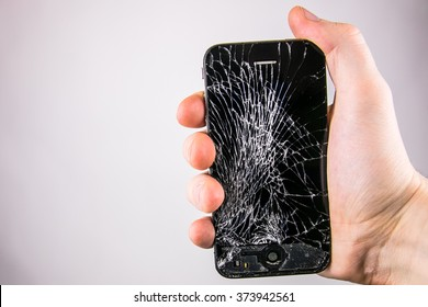 KAUNAS, LITHUANIA - FEBRUARY 8, 2016: Holding broken and screen cracked smartphone.  Broken Iphone 4
