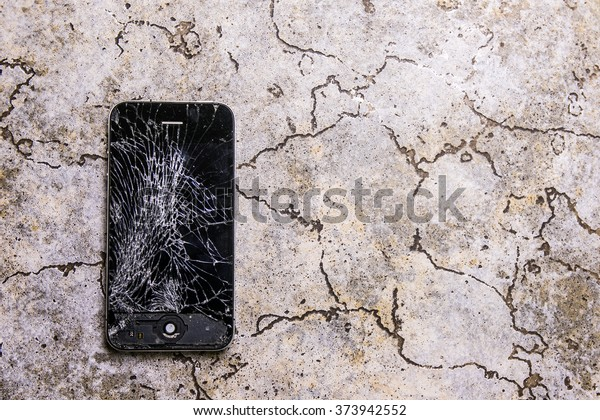KAUNAS, LITHUANIA - FEBRUARY 8, 2016: Fallen on floor and broken smartphone. Screen cracked iphone