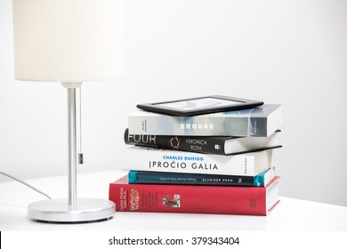 KAUNAS, LITHUANIA - FEBRYARY 19, 2016:  E-book (Amazon Kindle Paperwhite) lay on a few paper books. Isolated on white background