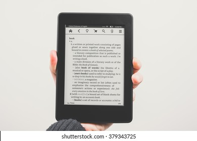 KAUNAS, LITHUANIA - FEBRYARY 19, 2016: Holding e-book reader (Amazon Kindle Paperwhite) in hand. Isolated on white background.