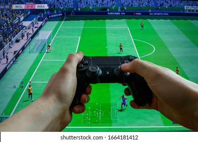 KAUNAS, LITHUANIA - MARCH 5, 2020: Man play video game on PlayStation 4 console. Point of view shot. Video games addiction. FIFA gameplay