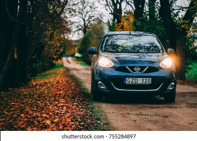KAUNAS, LITHUANIA - OCTOBER 2017 -  blue Nissan Micra parked in the natural sandy road. Yellow orange leaves in the bacground