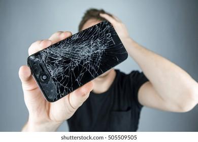 KAUNAS, LITHUANIA - OCTOBER 27, 2016: Sad man holds broken smartphone. Screen broken iphone. Not working phone