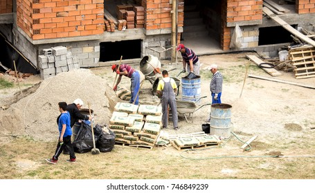 Kavadrarci, Macedonia (FYROM) - 7 May, 2017: The workers are mixing cement (concrete) using sand and rock for building of a new house in the residential area. Construction site.