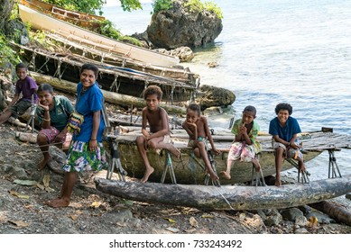 KAWA, TROBRIAND ISLANDS, PAPUA NEW GUINEA - NOVEMBER 13, 2016:  Young indigenous tribal children sit on their tribe's outrigger canoe on the poverty stricken island of Kawa in Papua New Guinea.