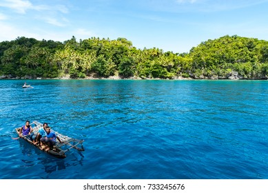 KAWA, TROBRIAND ISLANDS, PAPUA NEW GUINEA - NOVEMBER 13, 2016:  Indigenous tribal men paddle out in their outrigger canoe off the poverty stricken island of Kawa, Trobriand Islands, Papua New Guinea.
