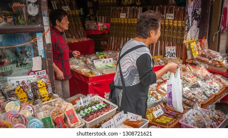 KAWAGOE, JAPAN - OCTOBER 11, 2016: Old, female shopkeepers selling cheap, small sweets, or also known as 'dagashi' in Japanese, in a typical Japanese shop called 'dagashiya'.